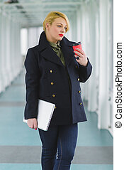 Portrait of blond businesswoman holding coffee and laptop in...