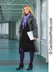 Portrait of blond businesswoman holding laptop - Portrait of...