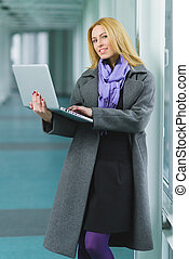 Portrait of blond businesswoman working on laptop in lobby.