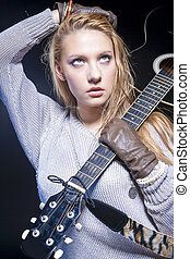 Portrait of Blond Caucasian Woman Posing With Acoustic Guitar Against Black Background