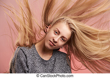 Portrait of blond girl with messy hair on pink background