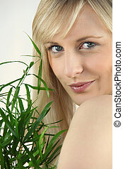 Portrait of blond holding green plant leaf