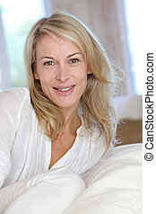Portrait of blond mature woman relaxing in sofa