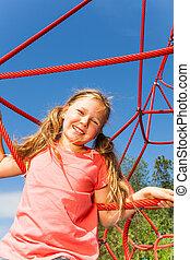 Portrait of blond smiling girl on net ropes