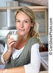 Portrait of blond woman drinking milk in home kitchen