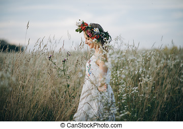 Portrait of blonde girl with blue eyes with a wreath of flowers on her head walking in field with white flowers