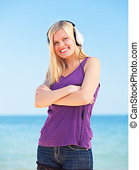 Portrait of blonde girl with headphone on the beach.