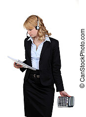 portrait of blonde in suit with headset holding notepad and calculator
