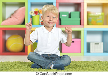Portrait of blonde little boy sitting on green carpet and with u