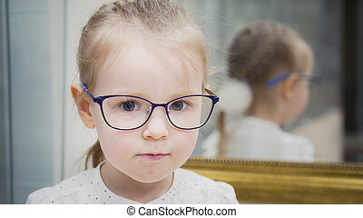 Portrait of blonde little cute girl in glasses at ophthalmology clinic