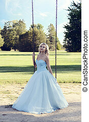 blonde woman in blue dress playing on swing