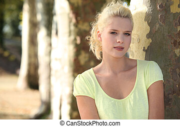 Portrait of blonde woman in front of tree trunks
