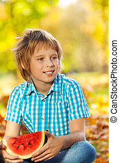 Portrait of boy holding watermelon on leaves