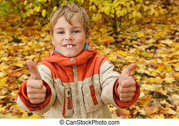 Portrait of boy in autumn park against fallen down leaves. Boy looks in camera having lifted thumbs of hands upwards.