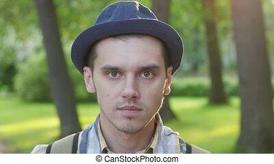Portrait of boy in hat showing anger, spite, malice....