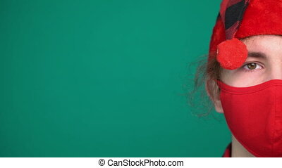 Portrait of boy in Santa hat wears a red medical mask, looking at camera
