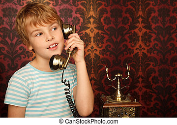 Portrait of boy in T-shirt talking to an old phone against wall with patterns.