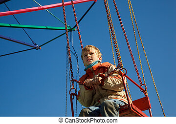 Portrait of boy seated in carousel. Bottom view on sunny autumn day.