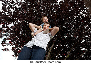 Portrait Of Boy Sitting On Father's Shoulders