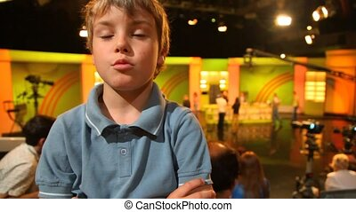 boy standing in big TV studio with spectators
