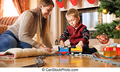 Portrait of boy with his mother playing on floor with toy train and railways. Child receiving presents and toys on New Year or Xmas