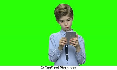 Portrait of boy with smartphone texting or playing.