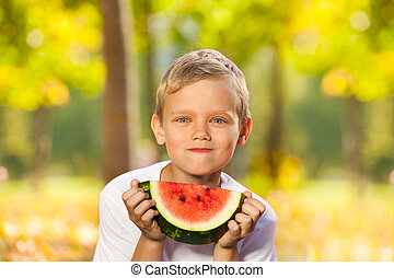 Portrait of boy with watermelon sitting in forest