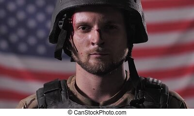 Close-up portrait of injured US soldier taking off helmet while posing against USA flag blurred on background. Proud face of wounded army male standing in front of United States flag