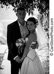 Portrait of bride and groom hugging under tree