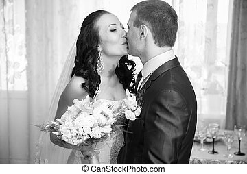 Portrait of bride and groom kissing at home
