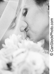 Portrait of bride and groom kissing passionately under veil