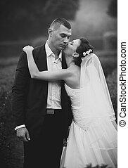 Portrait of bride kissing groom in cheek
