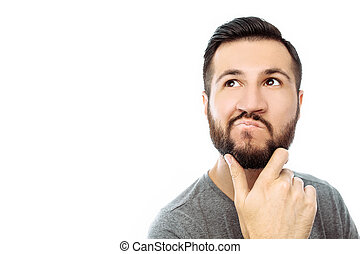 Portrait of brooding bearded man in grey t-shirt looking up and putting hand on face isolated on white background