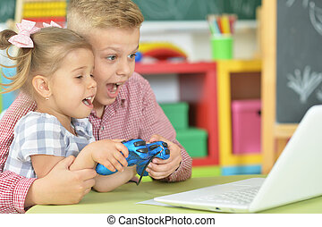 Portrait of brother and sister playing computer game