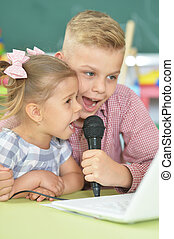 Portrait of brother and sister singing karaoke