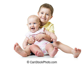 Portrait of brother hugging his little cute sister sitting on floor isolated on white background