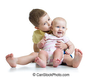 Portrait of brother kissing his little cute sister sitting on floor isolated on white background