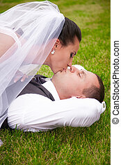 Portrait of brunette bride kissing groom lying on grass