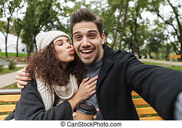 Portrait of brunette couple man and woman 20s taking selfie photo, while sitting on bench in green park