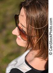 Portrait of brunette girl on sunny spring or summer day in park