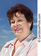 portrait of brunette pensioner woman smiling outdoor, blue sky