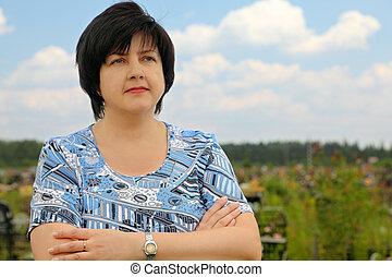 portrait of brunette plumpy mature serious woman, crossed hands, blue sky and clouds, cemetery