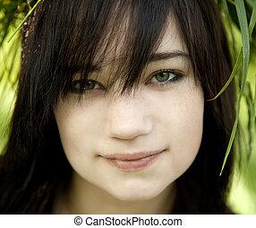 Portrait of brunette teen girl at green outdoor.