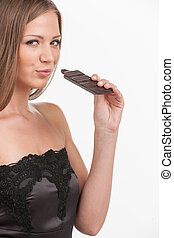 portrait of brunette woman biting chocolate. pretty girl holding chocolate over white background