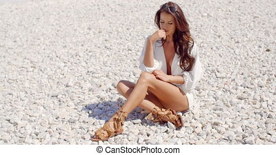 Portrait of Brunette Woman Sitting on Rocky Beach