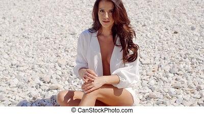 Portrait of Brunette Woman Sitting on Rocky Beach