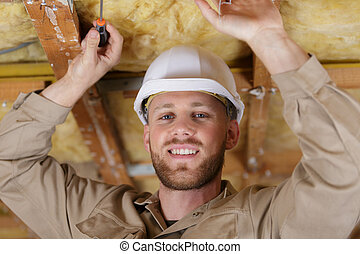 portrait of builder working on insulated ceiling