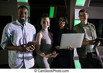 Portrait of business executives standing with laptop and digital tablet