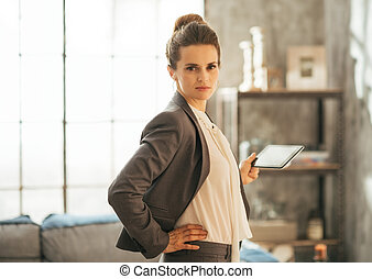 Portrait of business woman using tablet pc in loft apartment