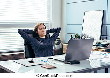 Portrait of business woman with hands behind head.